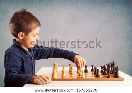 Kid playing chess on grunge background. - stock photo
