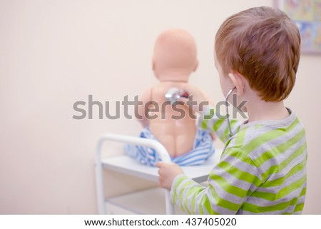 kid playing doctor with a stethoscope. boy playing with a doll and treats it. view from the back. copy space for your text - stock photo