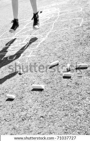 kid playing hopscotch on playground - stock photo