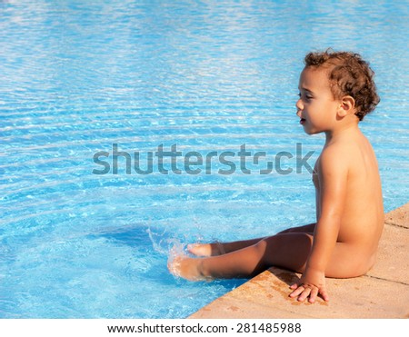 Kid playing in the pool with blue water. - stock photo