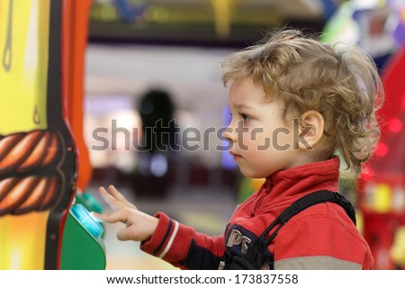 Kid playing on game machine at an amusement park