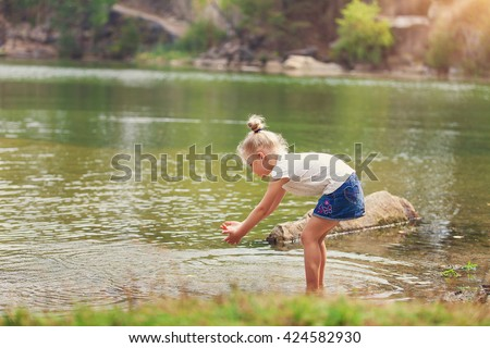 Kid playing on the beach in water