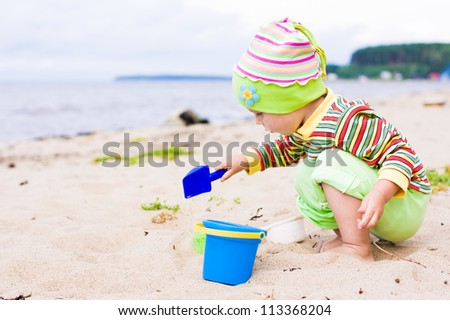 Kid playing on the beach with the children's shovel and a bucket.