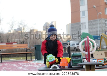 Kid playing on the playground in spring - stock photo