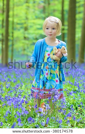 Kid playing outdoors. Adorable funny child, blonde healthy toddler girl enjoying nature, playing, hiking and hiding behind the tree in spring or summer forest with bluebells flowers - stock photo