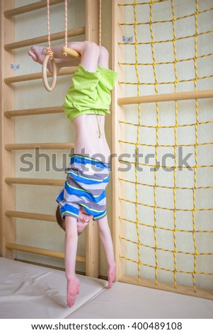 Kid playing sports on the gymnastic crossbar in the gym class.