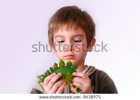 Kid playing with a dinosaur toy