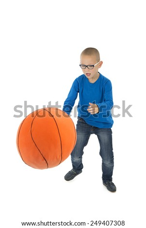 Kid playing with a huge basketball ball against a white background - stock photo