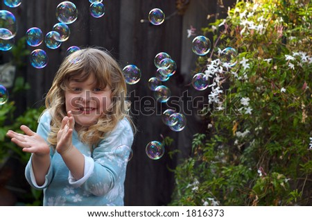 kid playing with bubbles - stock photo
