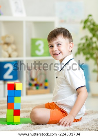 kid playing with building blocks at home or kindergarten - stock photo