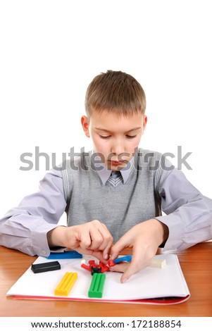 Kid playing with colorful plasticine at the School Desk