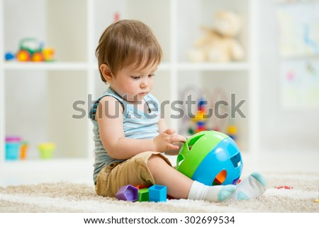 kid playing with logical toy on soft carpet in children room - stock photo