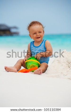 Kid playing with sand sitting on the Maldivian beach - stock photo