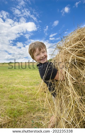 Kid playing with straw in a sunny summer day - stock photo