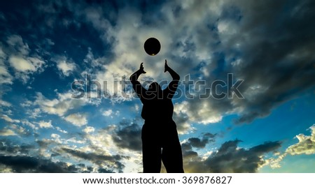 Kid plays with ball during evening in silhouette