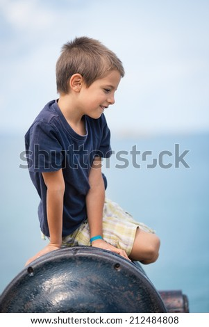 Kid portrait outdoors sit on gun in the city of Saint Malo, France. - stock photo