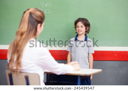 Kid questioned at school in front of chalkboard.