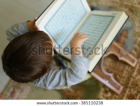 Kid reading Koran (the page is blurred) - stock photo