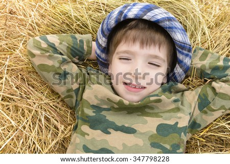 Kid relaxing on straws dreaming in a summer day - stock photo