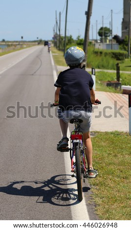 Kid riding a bicycle with the protective helmet along the paved road - stock photo