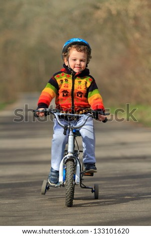 Kid riding his bike on the forest road - stock photo