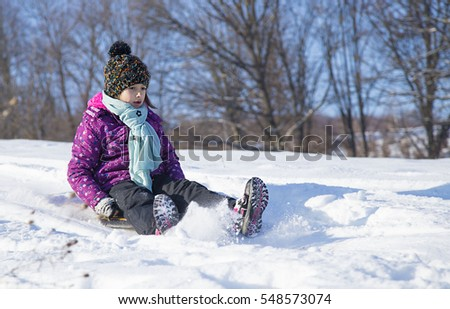 kid riding on snow slides in winter time