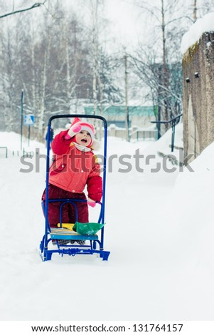 Kid rolls sleigh in winter on snow.