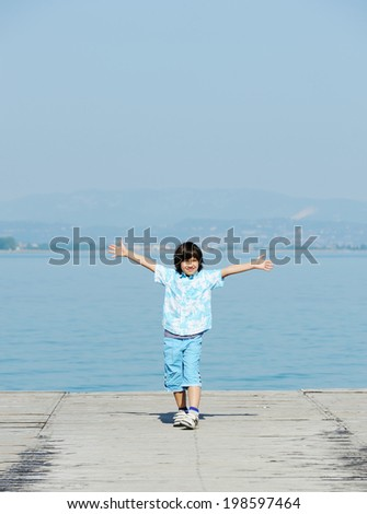 Kid running and jumping on dock