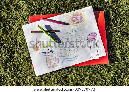 Kid's drawing with colorful pens on grass