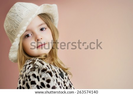 Kid's fashion background.Lovely child girl portrait. Young model posing in hat and fur coat. - stock photo