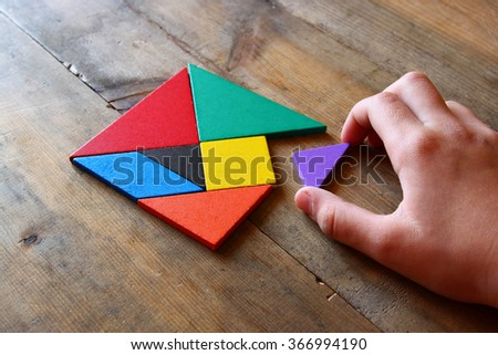 kid's hand holding a missing piece in a square tangram puzzle, over wooden table.  - stock photo