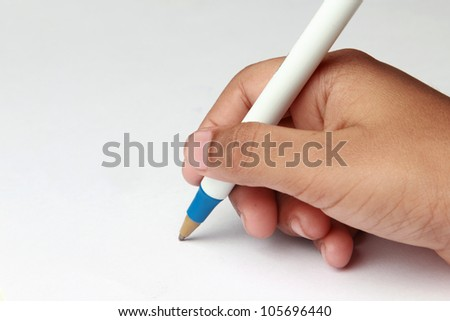 Kid's hand holding a pen against a white paper background