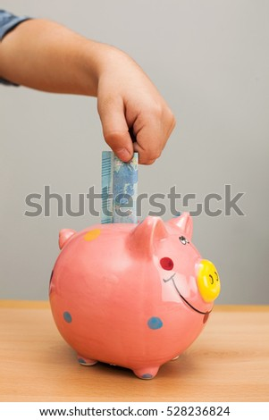 Kid's hand put a banknote into a pink pig bank.