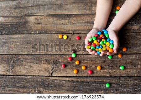 Kid's hands full of sweet candy - stock photo