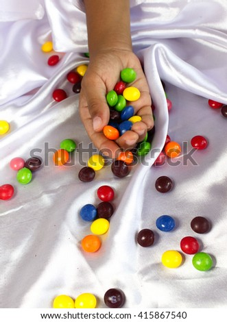 Kid's hands full of sweet candy