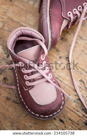 kid's leather shoes on wooden background - stock photo