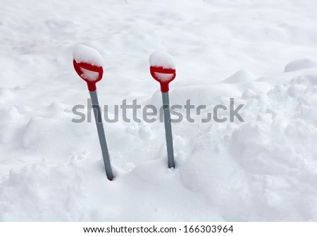 Kid's shovels left in the snow bank before a snowfall - stock photo