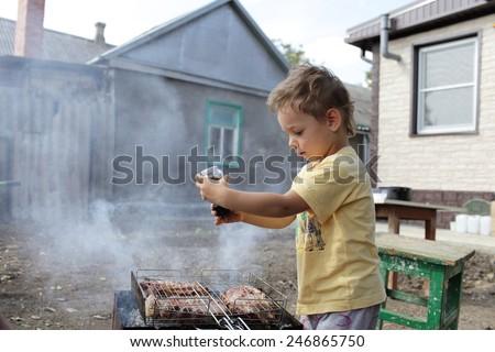 Kid seasoning pork chops with pepper at the backyard - stock photo