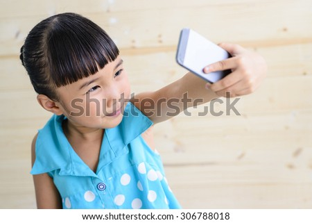 Kid selfie by smartphone with blur wood background