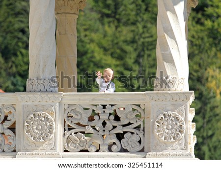 Kid sending greetings from a balcony - stock photo