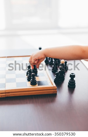 Kid setting a black chess piece on the chessboard with copy space - stock photo