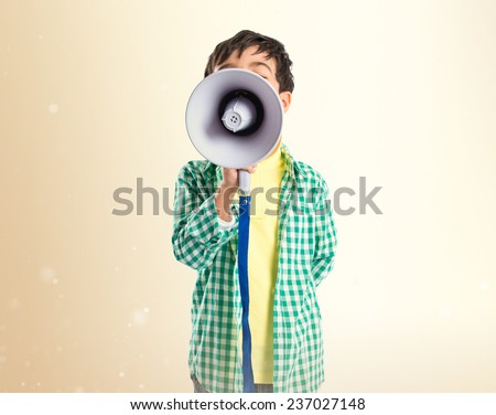 Kid shouting by megaphone over ocher background  - stock photo