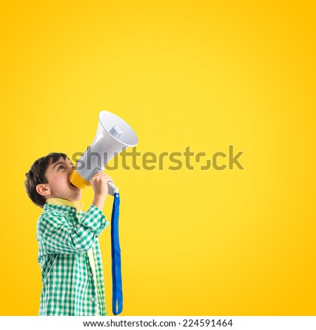 Kid shouting by megaphone over yellow background - stock photo