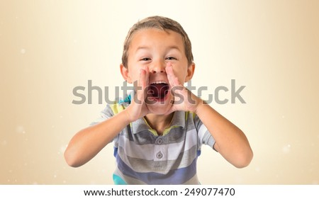 Kid shouting over ocher background - stock photo