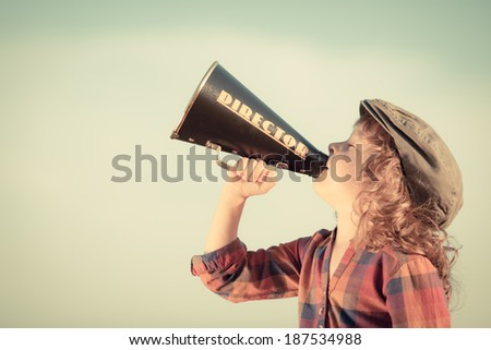 Kid shouting through vintage megaphone. Child having fun outdoors. Communication concept. Summer sky background as copyspace for your text - stock photo