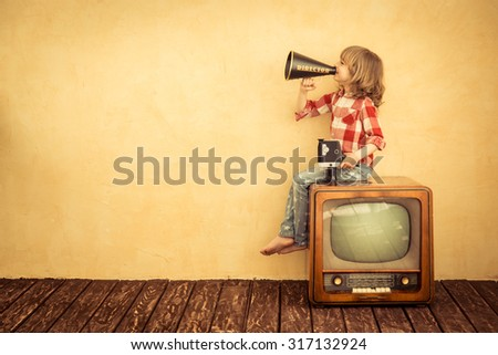 Kid shouting through vintage megaphone. Communication concept. Retro TV - stock photo
