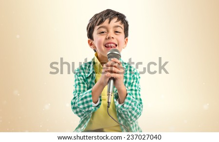 Kid singing over ocher background  - stock photo