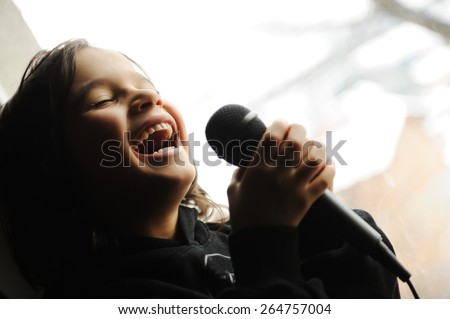 Kid singing song with microphone - stock photo