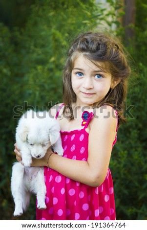 kid sitting and holding puppy - stock photo