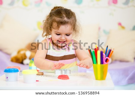 kid sitting at table playing with colorful clay - stock photo